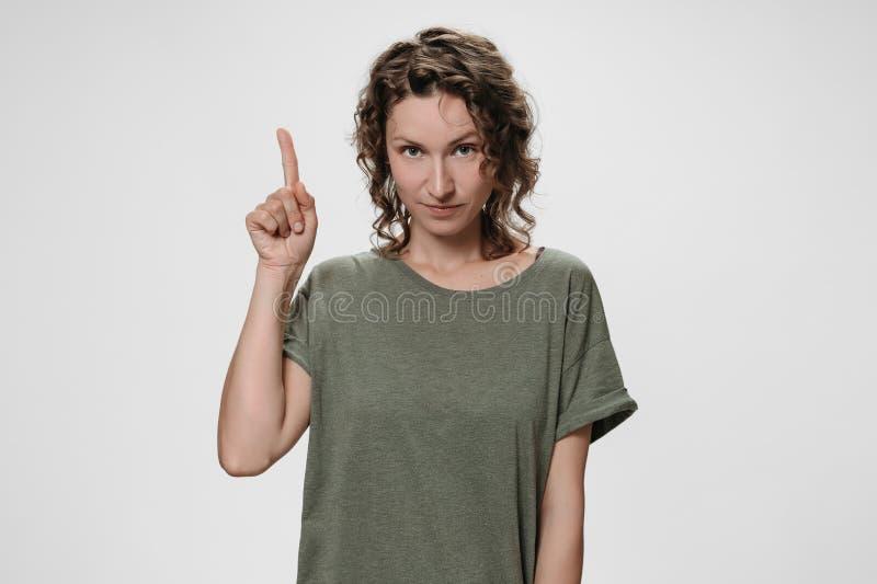 Porträt der jungen gelockten Frau zeigt mit dem Vorderfinger oben, zeigt Platz an stockfotografie