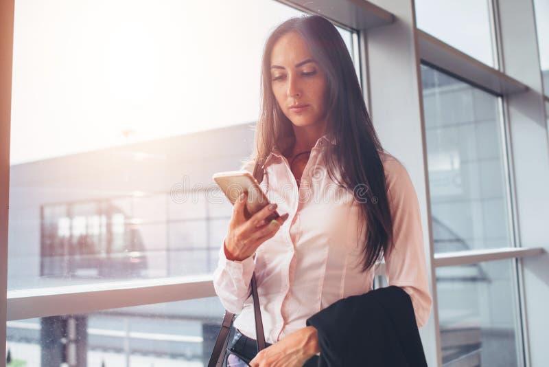 Porträt der jungen Geschäftsfrau, die Smartphone beim Gehen zu verschalendem Bereich im Flughafen verwendet stockbilder