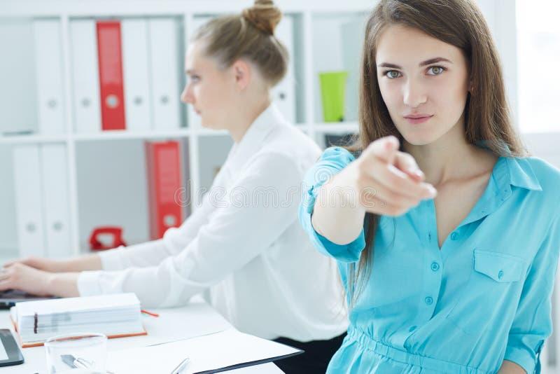 Porträt der jungen Geschäftsfrau gerade zeigend auf das lächelnde cameraand, mit weiblichem Kollegen auf dem Hintergrund lizenzfreies stockfoto