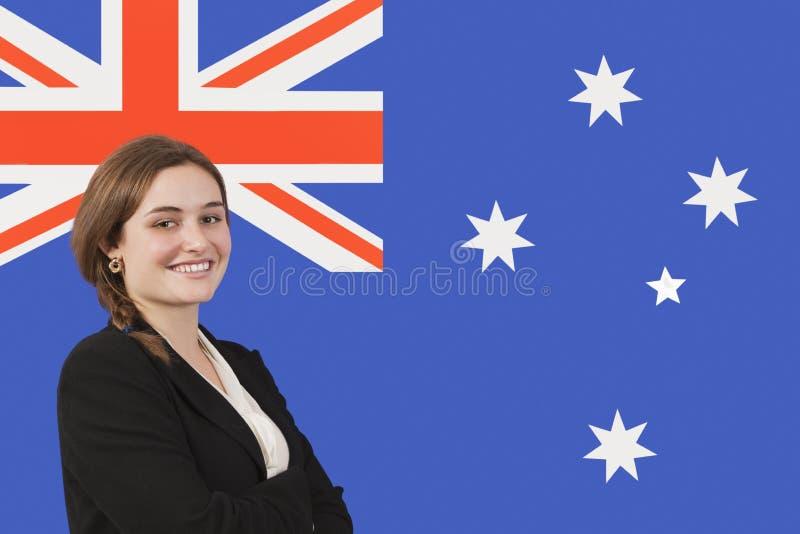 Porträt der jungen Geschäftsfrau lächelnd über australischer Flagge lizenzfreie stockfotografie
