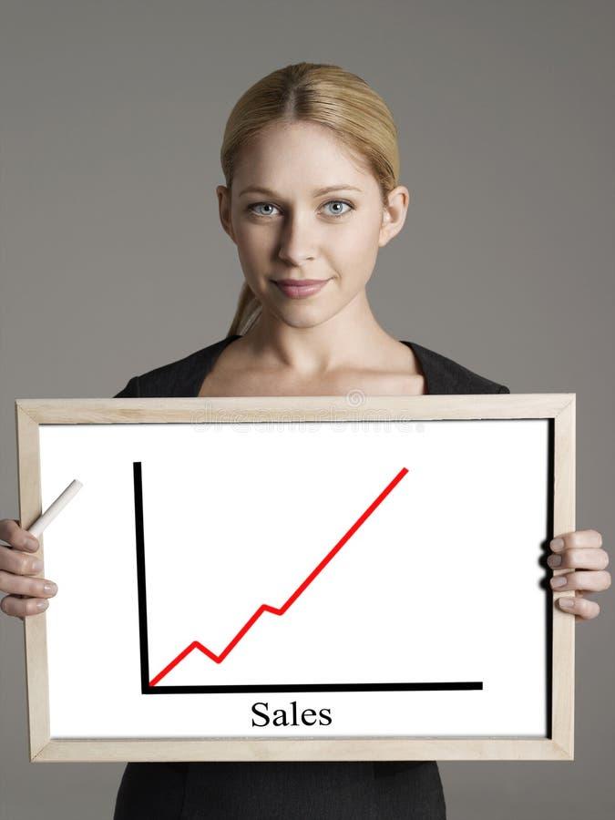 Porträt der jungen Geschäftsfrau Verkaufsdiagramm gegen grauen Hintergrund zeigend lizenzfreies stockfoto