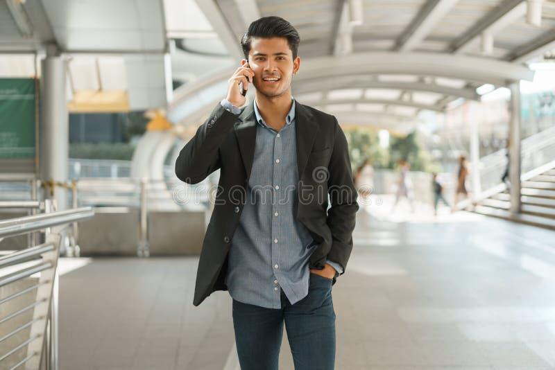Porträt der jungen Geschäftsmannstellung im äußeren Büro und der Unterhaltung auf Smartphone Asiatischer Geschäftsmann-Abnutzungs stockfoto