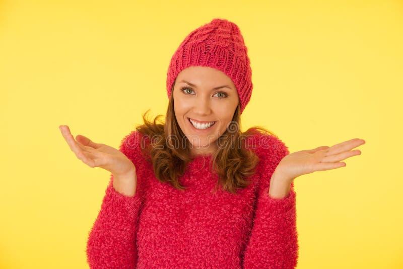 Porträt der jungen glücklichen Frau in der rosa flaumigen Strickjacke und in der rosa Strickmütze auf gelbem Hintergrund stockbilder