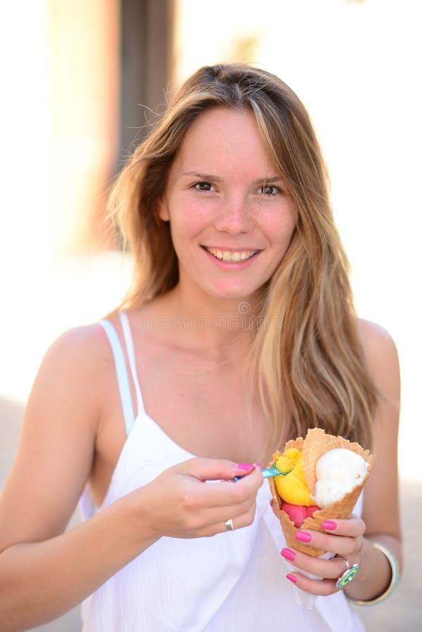Porträt der jungen glücklichen Frau, welche die Eiscreme im Freien isst stockfoto
