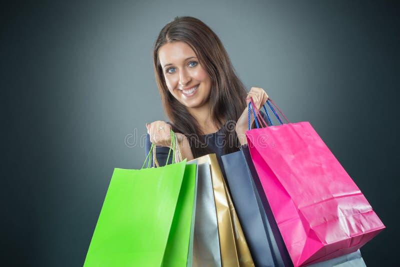 Porträt der jungen glücklichen lächelnden Frau mit Einkaufstaschen Kreditkarte und Schuhe stockfotos