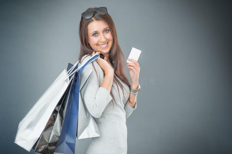 Porträt der jungen glücklichen lächelnden Frau mit Einkaufstaschen Kreditkarte und Schuhe stockbild