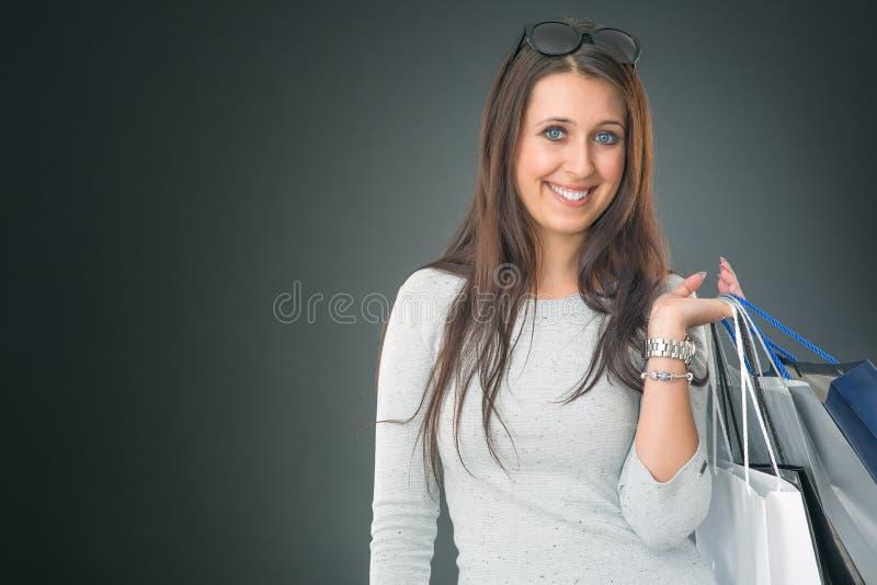 Porträt der jungen glücklichen lächelnden Frau mit Einkaufstaschen Kreditkarte und Schuhe lizenzfreie stockbilder