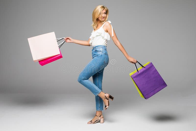 Porträt der jungen glücklichen lächelnden Frau mit schwarzem Freitag-Einkaufen der Einkaufstaschen lizenzfreies stockfoto
