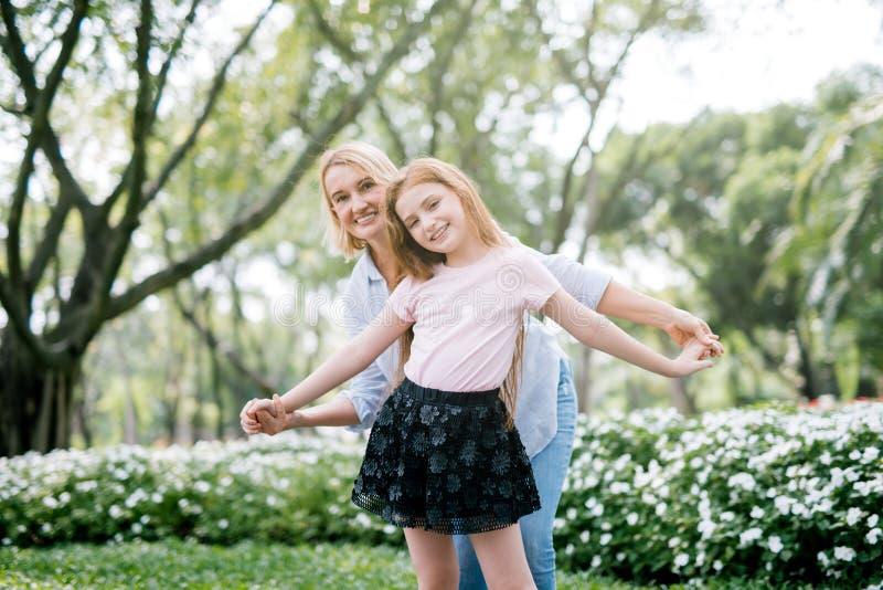 Porträt der jungen glücklichen schönen Mutter und der Tochter, die zusammen am Park spielt stockbilder
