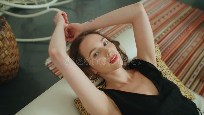 Porträt der jungen hübschen Brunettefrau, die auf Sofa liegt und zu einer Kamera lächelt stockfoto
