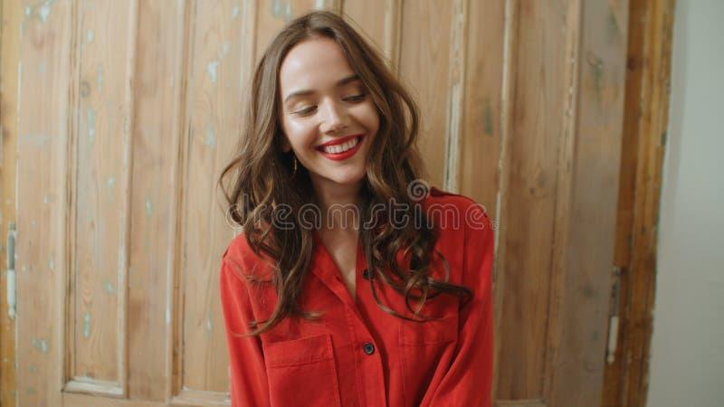 Porträt der jungen hübschen Brunettefrau, die zu Hause lächelt stockbilder