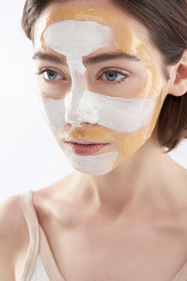 Porträt der jungen hübschen Frau mit Gesichtsmaske lizenzfreie stockfotografie