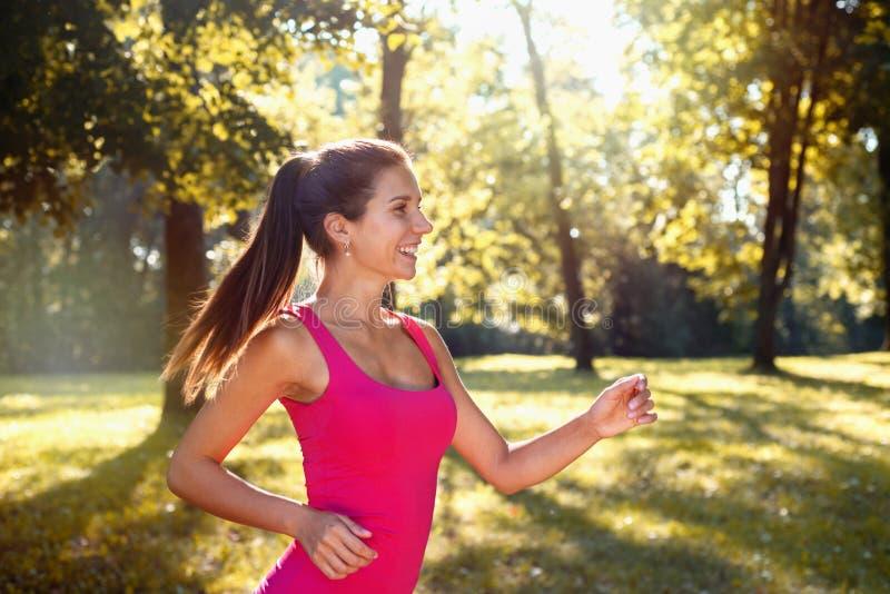 Porträt der jungen, im Park im Freien lebenden Smahlerin sportliche Brunette lizenzfreies stockbild