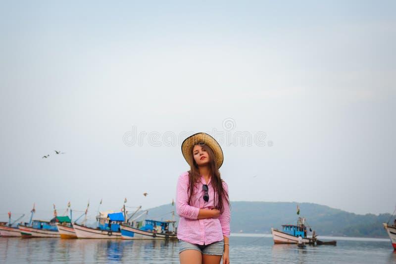 Porträt der jungen kaukasischen Frau im Strohhut und der kurzen Denimkurzen hosen an einem warmen bewölkten Tag Sch?ner langhaari stockbild