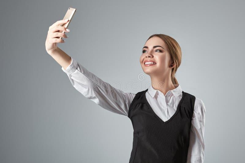 Porträt der jungen kaukasischen Geschäftsfrau in der Klage, die selfie am Telefon tut lizenzfreie stockbilder