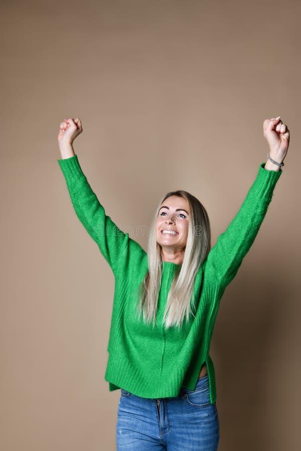 Porträt der jungen kaukasischen, süßen, erfolgreichen Frau, die Sieg mit den angehobenen Fäusten, lächelnd feiert stockfotografie