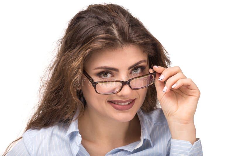 Porträt der jungen lächelnden Frau, die über Brillen schaut lizenzfreie stockbilder