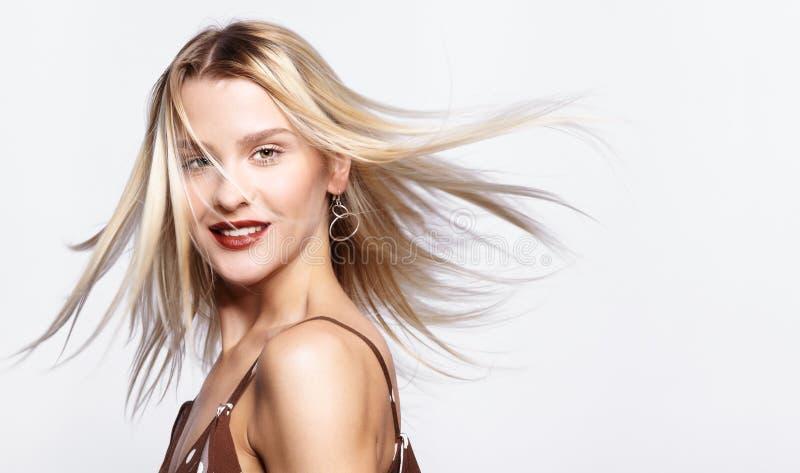 Porträt der jungen lächelnden Frau der Schönheit mit dem rauhaarigen Haar auf dem Wind lizenzfreie stockfotos