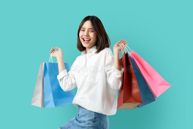 Porträt der jungen lächelnden zufälligen Kleidung der asiatischen Frau, die mehrfarbige Einkaufstaschen auf hellblauem Hintergrun stockbild