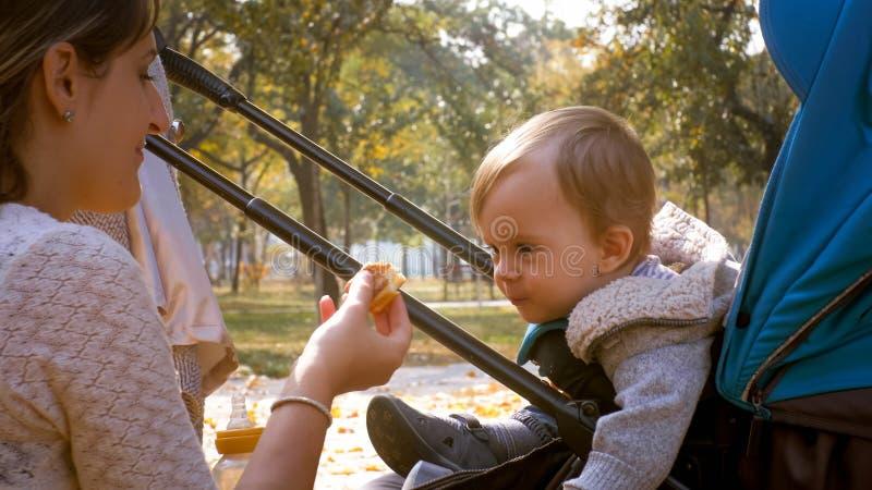 Porträt der jungen Mutter ihren Kleinkindjungen einziehend, der im Spaziergänger am Park sitzt stockbilder