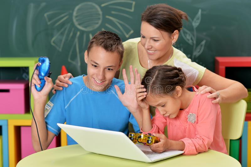 Porträt der jungen Mutter mit den Kindern, die Computerspiel mit Laptop spielen lizenzfreies stockbild