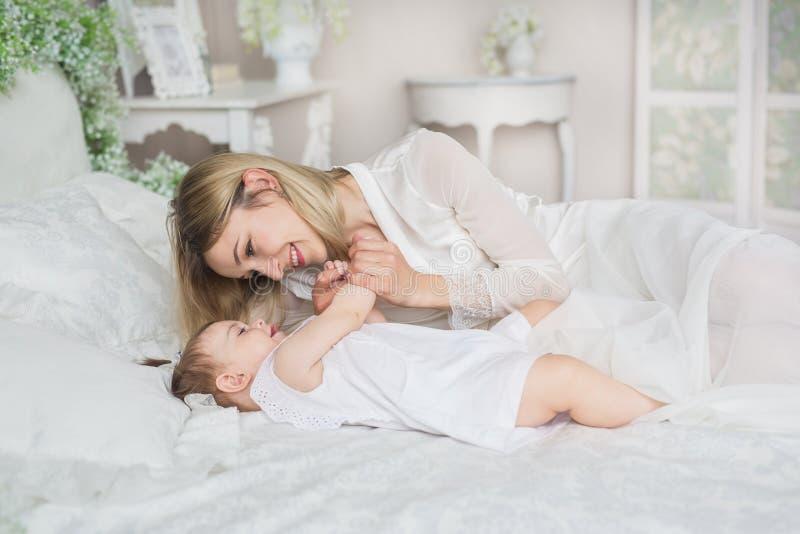 Porträt der jungen Mutter spielt mit ihrem kleinen Baby auf einem Bett stockbild