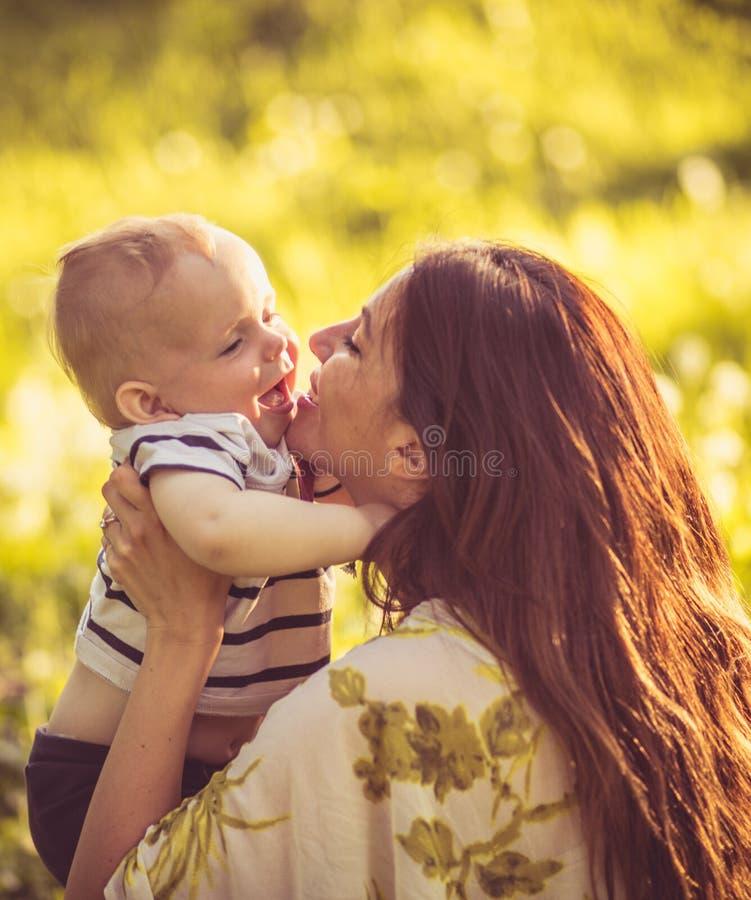 Porträt der jungen Mutter und ihres Babys, Zeit für Küsse stockfotos