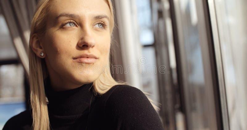 Porträt der jungen nachdenklichen Frau, die Restaurantfenster betrachtet lizenzfreie stockfotos