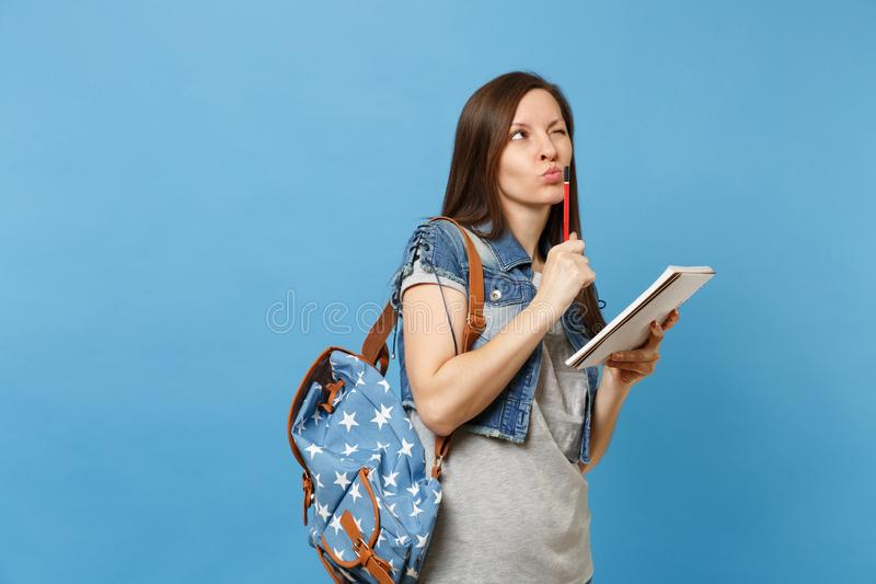 Porträt der jungen nachdenklichen Studentin in der Denimkleidung mit dem Rucksack, der Prüfung denkend an Testholdingnotizbuch ni lizenzfreie stockbilder
