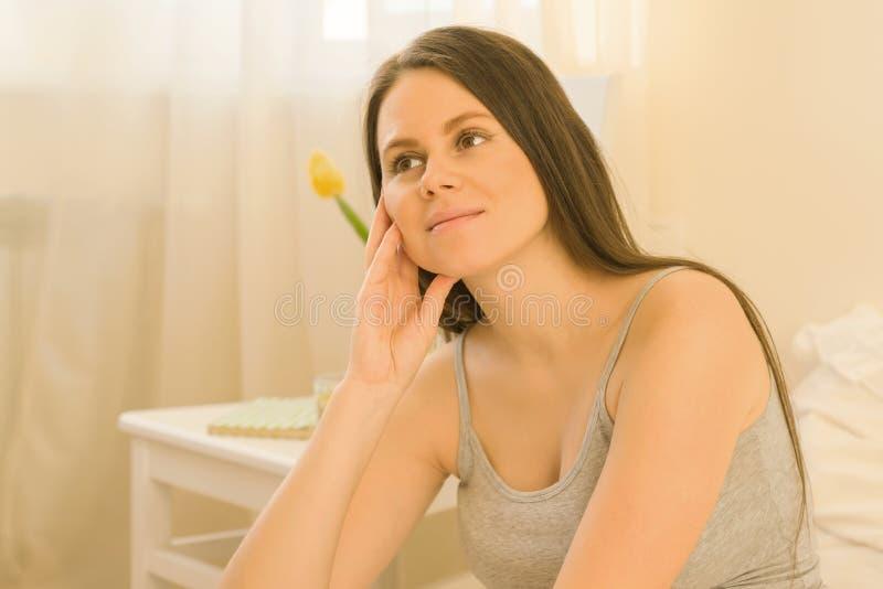 Porträt der jungen romantischen schönen brunette Frau, die zu Hause im Bett sitzt, Frau schaut träumerisch weg, sonniger Schlafzi lizenzfreies stockfoto
