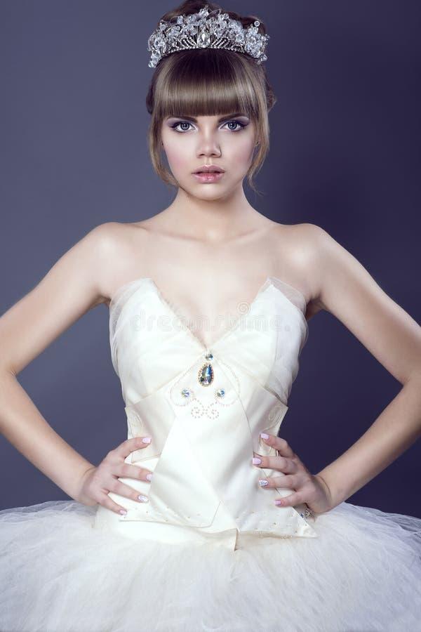 Porträt der jungen schönen Ballerina im tragenden weißen Korsett und in Ballettröckchen der Juwelkristallkrone, die mit ihren Hän stockfotografie