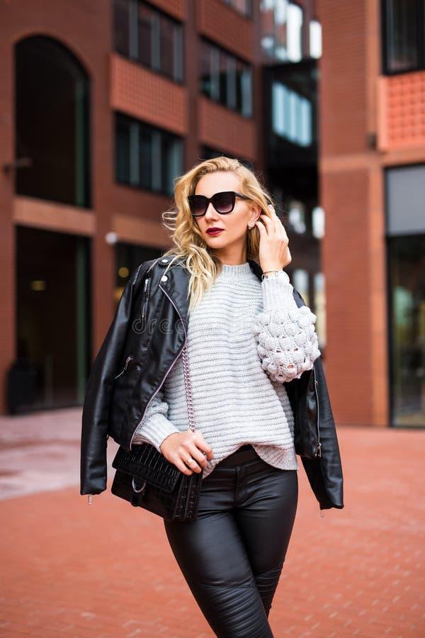 Porträt der jungen schönen blonden Frau, die auf der Straße aufwirft lizenzfreie stockbilder