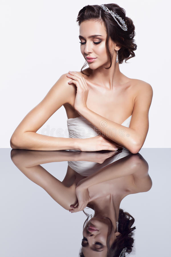 Porträt der jungen schönen Brunettefrau, die am Spiegelvorsprung sitzt stockfotografie