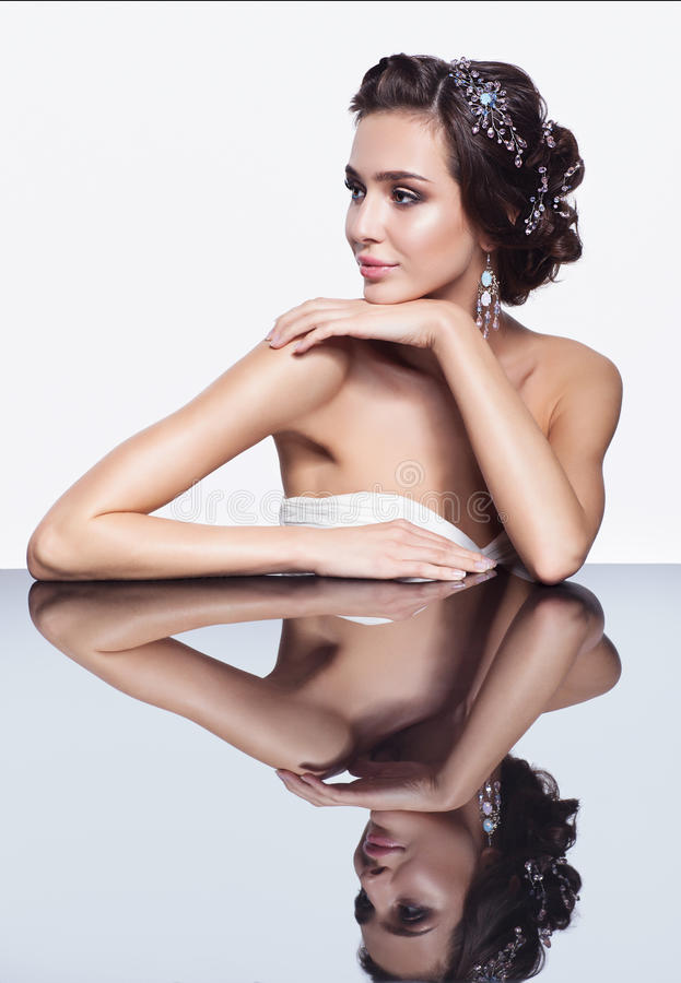 Porträt der jungen schönen Brunettefrau, die am Spiegelvorsprung sitzt lizenzfreie stockfotos