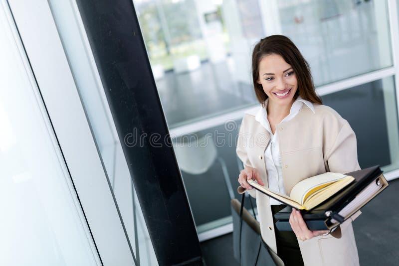 Porträt der jungen schönen Geschäftsfrau, die zum Büro geht lizenzfreie stockfotografie