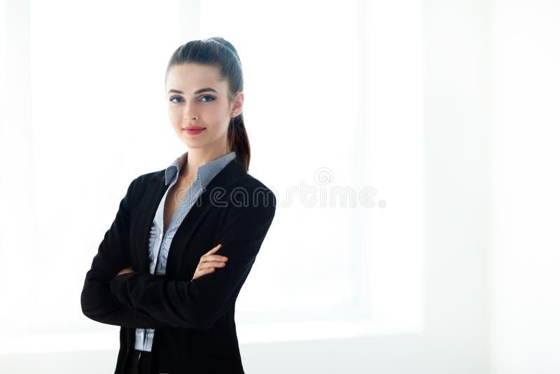 Porträt der jungen schönen Geschäftsfrau mit den gekreuzten Armen lizenzfreies stockbild