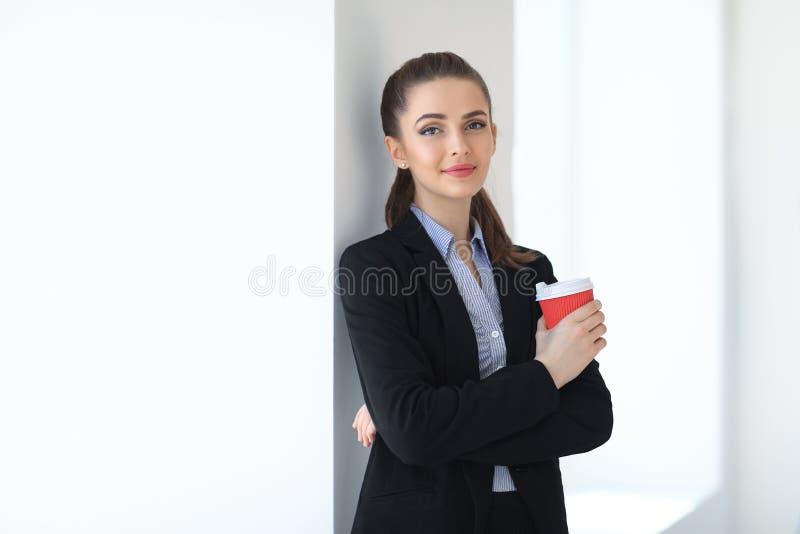 Porträt der jungen schönen Geschäftsfrau mit Tasse Kaffee herein lizenzfreie stockbilder