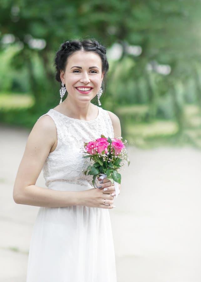 Porträt der jungen schönen glücklichen lächelnden Brautfrau mit dem Hochzeitsblumenstrauß, der Kamera im Sommergrünpark untersuch lizenzfreie stockfotos