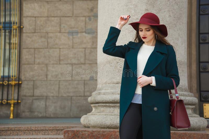 Porträt der jungen schönen modernen Frau, die auf Straße aufwirft Dame, die stilvollen roten Hut und Handtasche, Smaragd trägt stockfotografie
