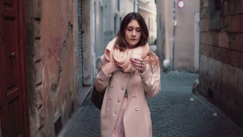 Porträt der jungen schönen modernen Frau, die an der Stadt geht Mädchen geht, am Morgen und an trinkendem Kaffee zu arbeiten lizenzfreie stockfotografie