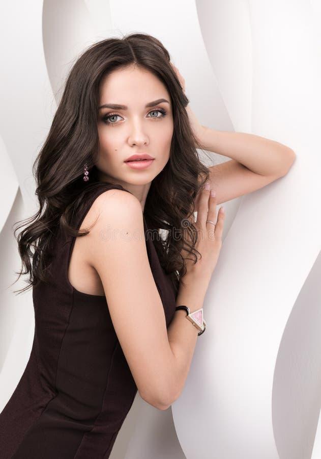 Porträt der jungen Schönheit im braunen Kleid in einer gewellten Wand lizenzfreies stockfoto