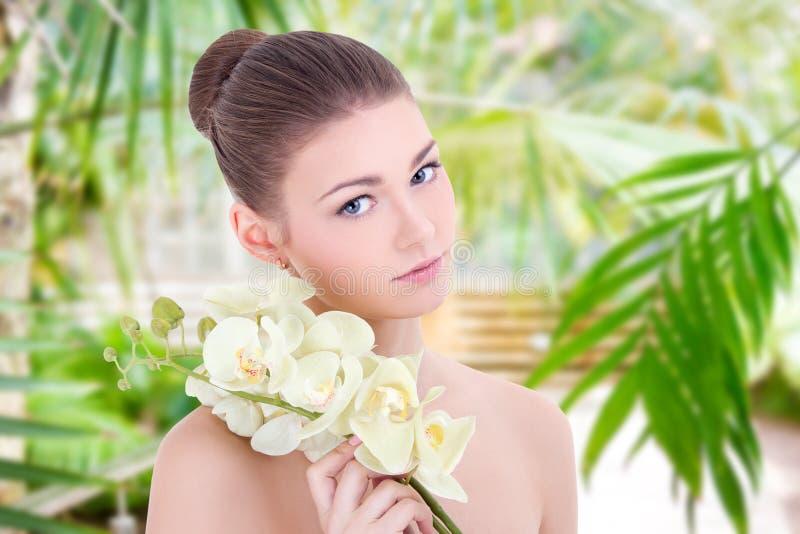 Porträt der jungen Schönheit mit Orchideenblumen über grünem Hintergrund stockfoto