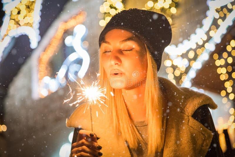 Porträt der jungen Schönheit mit Wunderkerze vor Weihnachtsdekoration draußen lizenzfreie stockbilder