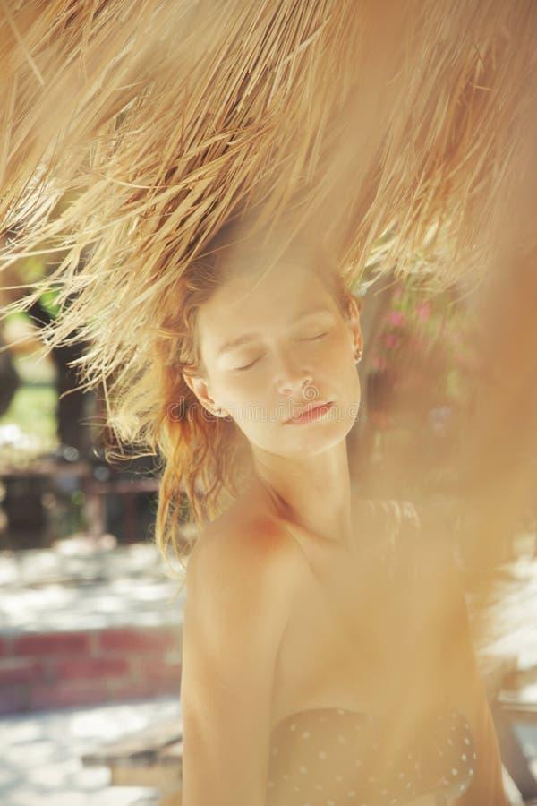 Porträt der jungen Schönheit unter Strandschirm lizenzfreies stockfoto