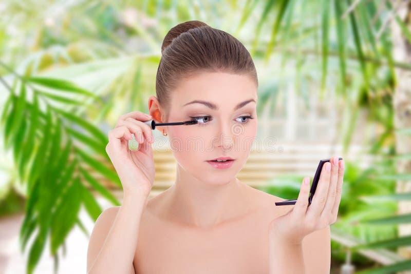 Porträt der jungen Schönheit Wimperntusche auf ihren Wimpern über Sommerhintergrund anwendend lizenzfreies stockfoto