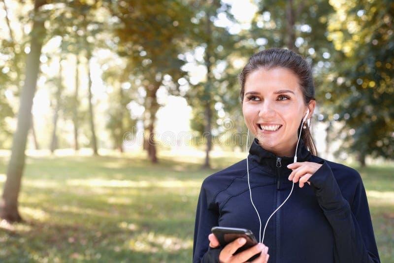 Porträt der jungen, sportlich gefräßigen Brunette-Frau, die mit Kopfhörern im Park im Freien läuft lizenzfreie stockbilder