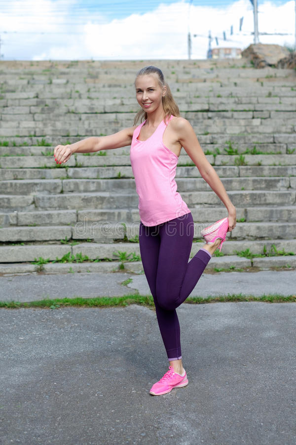 Porträt der jungen sportlichen Frau im Sportkleid tut das Ausdehnen Übungen von den im Freien lizenzfreie stockfotos