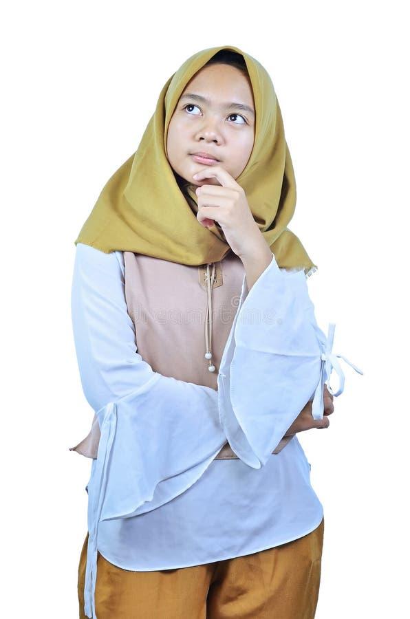 Porträt der jungen Studentenfrau, die oben zum copyspace denkt und schaut stockfotografie