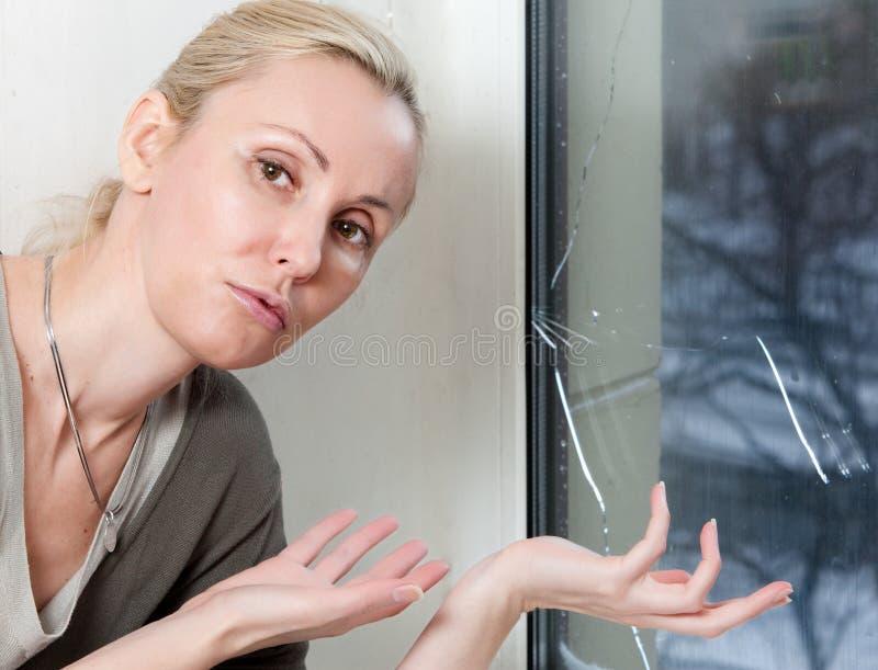 Porträt der jungen Umkippenfrau der Hausfrau am Fenster, die von einem Frost mit einem doppelverglasten Fenster gesprengt haben stockbild