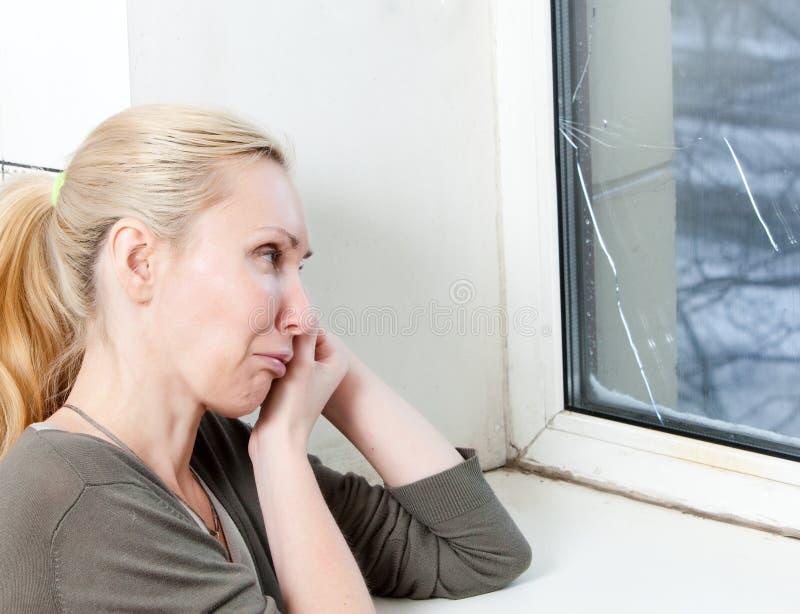 Porträt der jungen Umkippenfrau der Hausfrau am Fenster, die von einem Frostfenster gesprengt haben stockfotografie